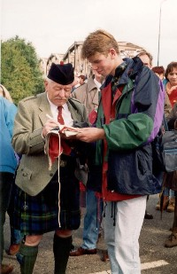 A Scottish veteran is signing a Dutch flag with his name and unit